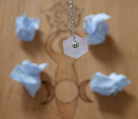 Rose quartz crystal pendulum dowsing a set of options over an oak board.