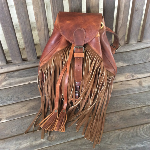 Fringed top grain leather backpack accented handwoven repurposed huipil.