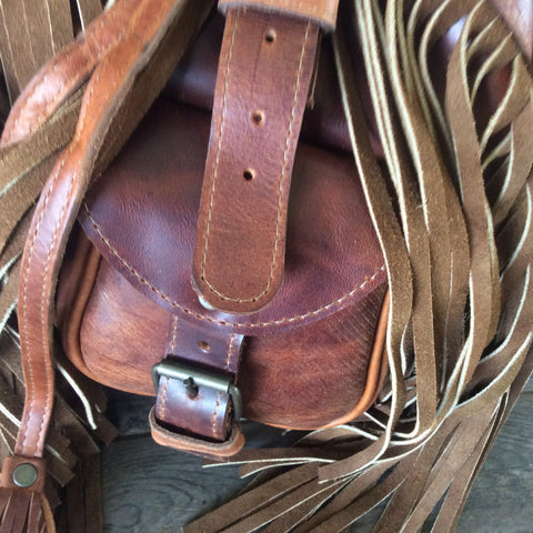 Fringed top grain leather backpack accented handwoven repurposed huipil