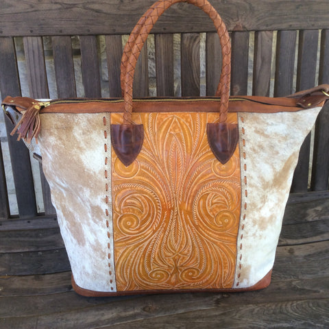 Handmade, hair on hide, hand tooled leather travel bag.