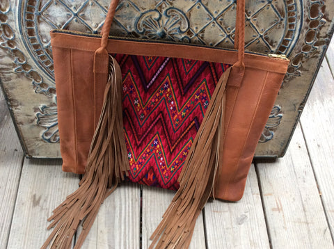 Hand stitched Boho top grain leather fringed tote bag with accented handwoven fabric.