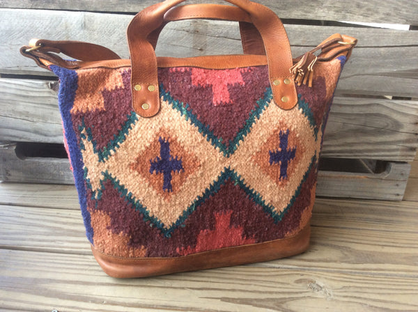 Ethinic carpet and tribal bag hand tufted wool, oil rubbed leather travel bag.