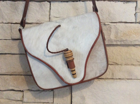 Leather trimmed with unique hand carved wooden piece light colored cowhide purse