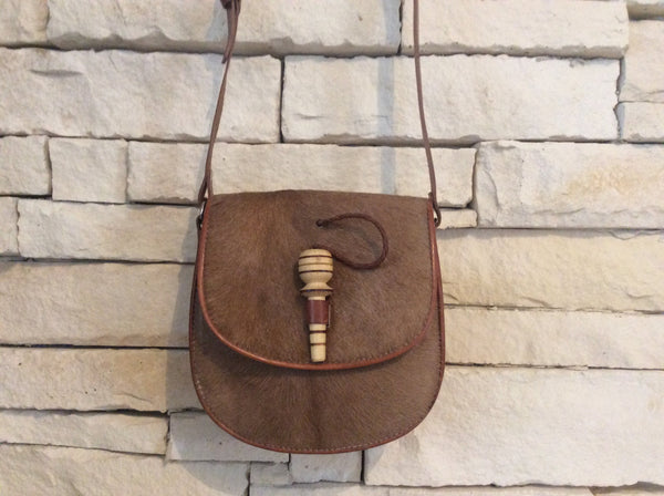Brown cowhide leather purse with hand carved wooden dowel closure.