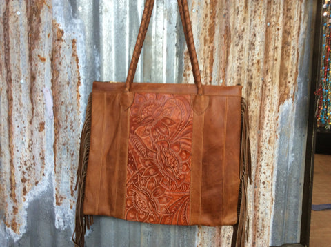 Hand tooled, oiled rubbed, hand stitched  leather accented with fringe purse or tote.