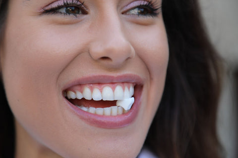 A woman demonstrating how Movemints clear aligner mints fit between your top and bottom teeth