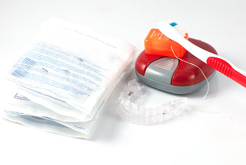 Bags of clear aligner sets next to retainer case and toothbrush