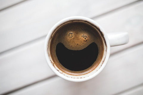 Cup of coffee with foam edited to look like a smile