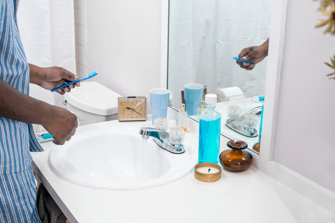 Picture of person in bathroom holding toothbrush