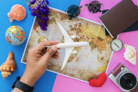 Map of the world with hand holding a model plane and other travel accessories