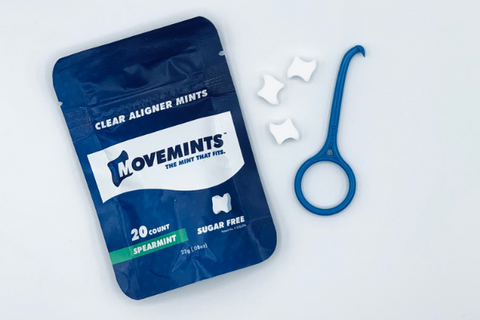 One bag of Movemints clear aligner mints (20 count), one blue OrthoKey and three loose mints showing the mint's patented grooves