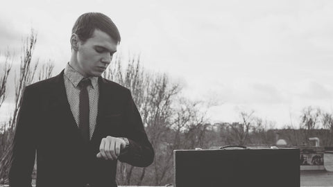 black and white young business man checking watch outside winter