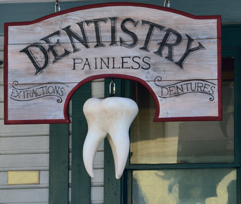 Old fashioned sign for painless dentistry included in a blog about clear aligners