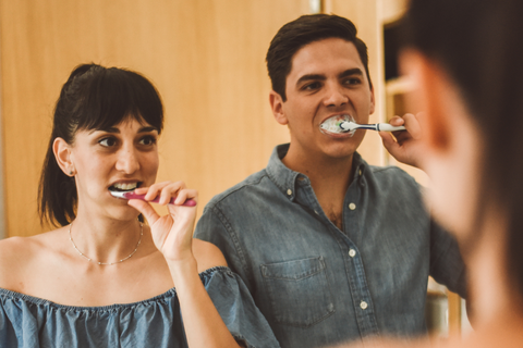 man and woman brushing their teeth together