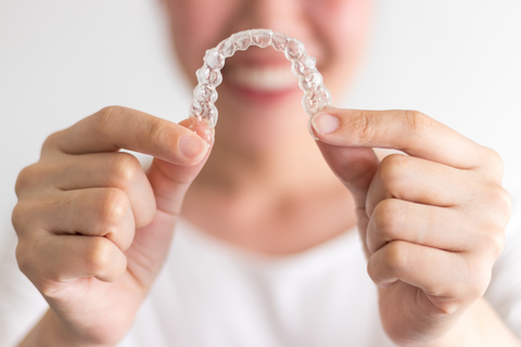 person holding invisalign trays
