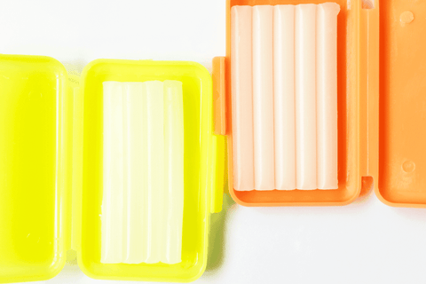two containers of dental wax orange and yellow