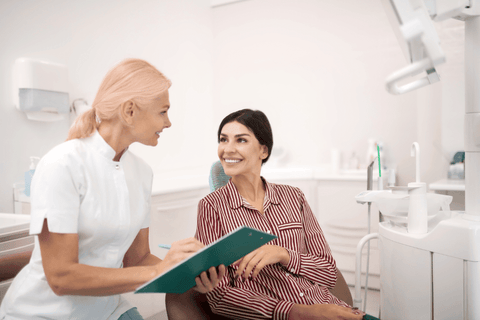 woman consulting dentist about care older dentist with clipboard giving advice