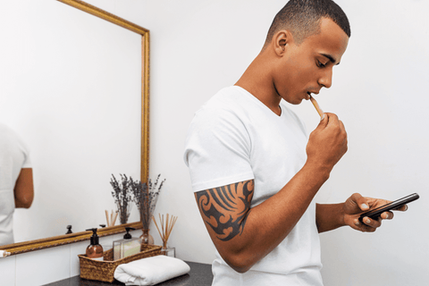 young man tattoos brushing teeth before bed on cell phone