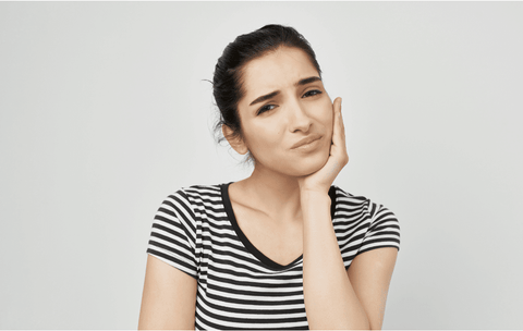 young woman clutching jaw due to tooth pain