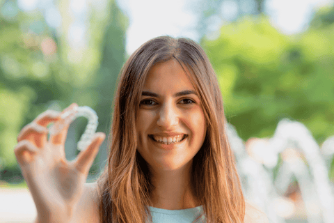 young woman holding up clear aligner outside smiling summer trees