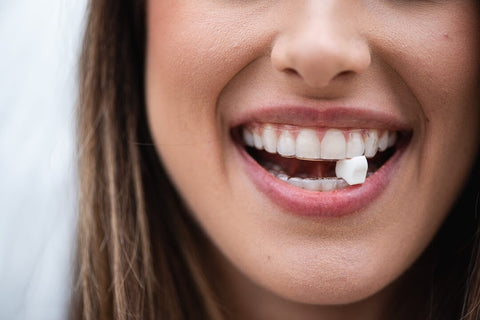 young woman using invisalign chewie movemint clear aligners smiling close up