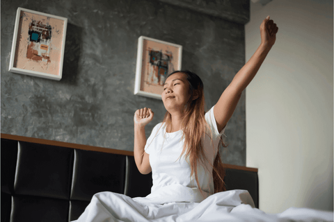 young woman waking up in the morning stretching refreshed sleep