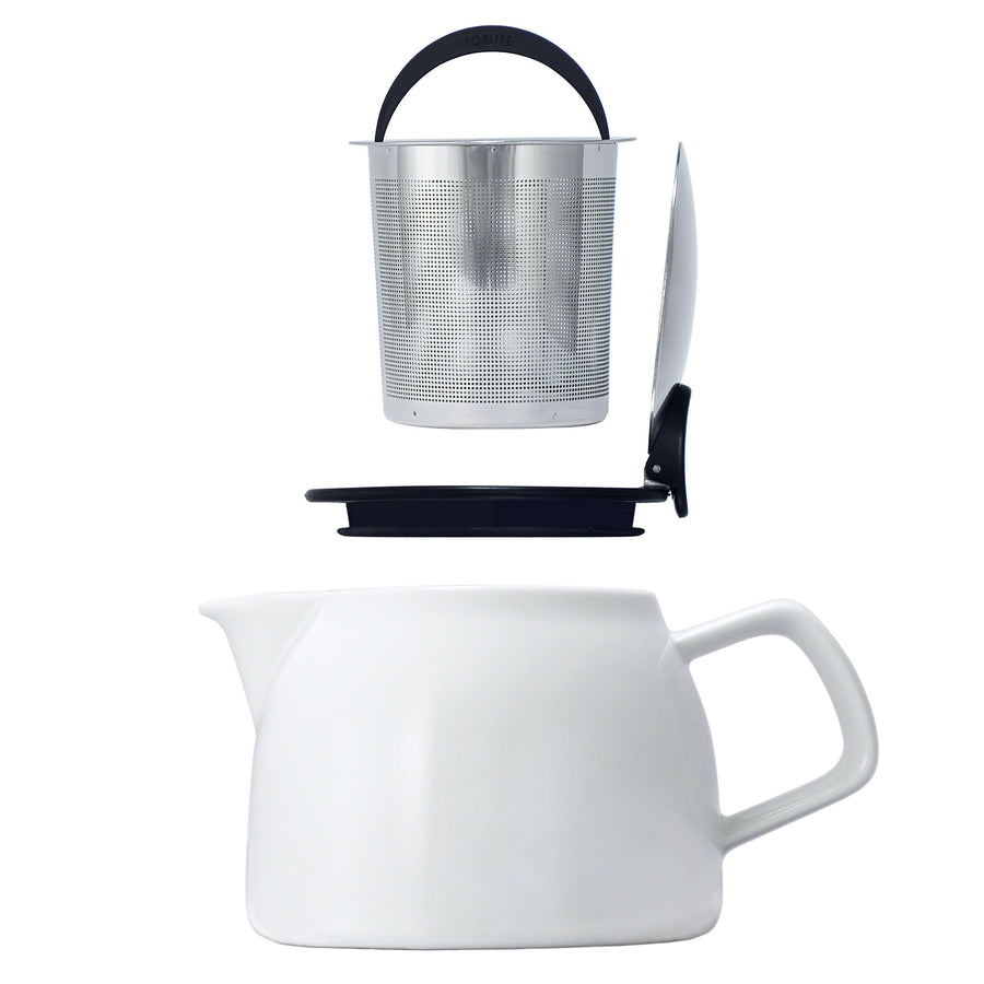 Tealula 16 oz bell-shaped White teapot with square handle and black and silver detachable push-on-lid next to silver removeable basket infuser