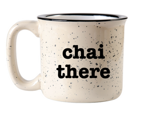 "off white camp mug with black speckles of paint on the surface and black rim circle handle and the words ""chai there"" in black font"