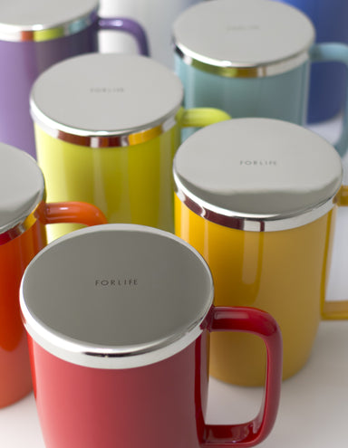 "a collection of TeaLula 18 oz mugs in various glossy surface colors with large thin rectangle handles and shiny stainless steel lids with ""For life"" text in the center of the lid"