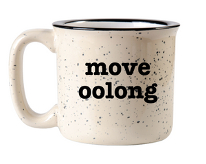 "off white camp mug with black speckles of paint on the surface and black rim circle handle and the words ""move oolong"" in black font"