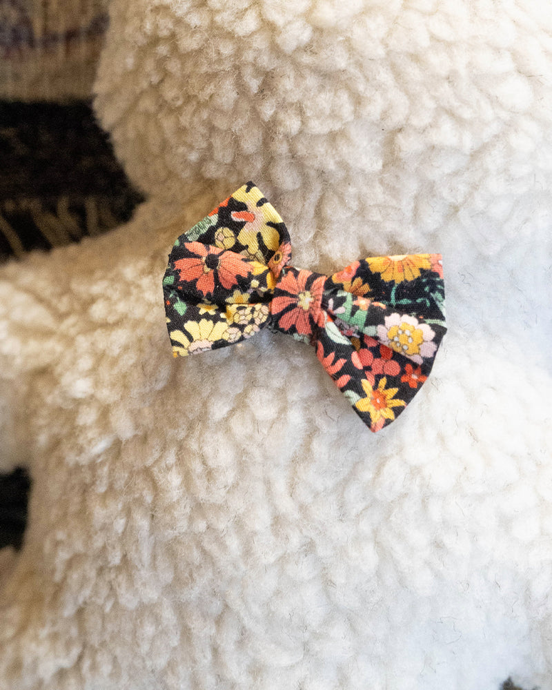 Plush Dog Toy filled with 100% organic lavender to help calm your pet. Wearing a black floral bowtie. Designed to give back 100%.