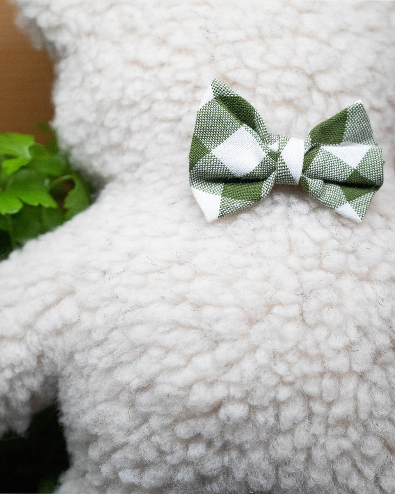 Plush Dog Toy filled with 100% organic lavender to help calm your pet. Wearing a green gingham bowtie. Designed to give back 100%.