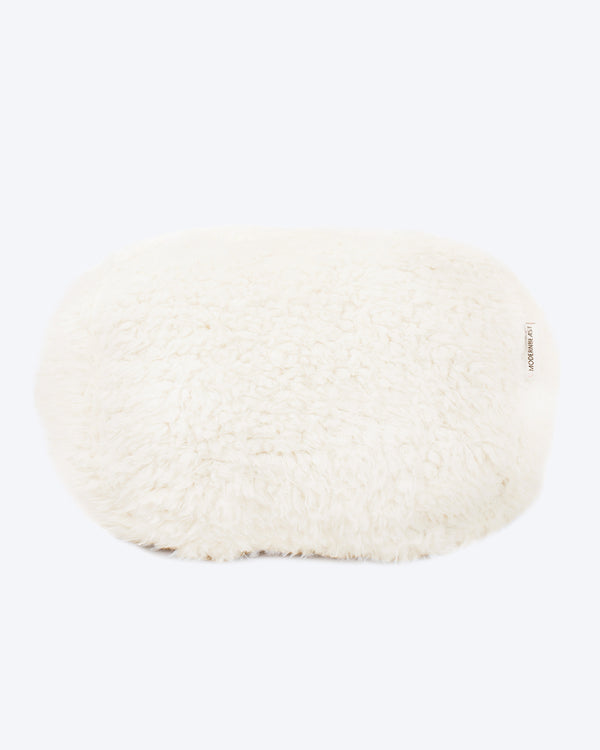 A dog bed is in ivory soft material, available in small and large sizes and made out of recycled materials.
