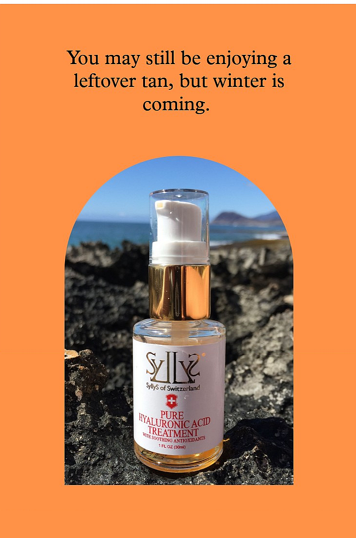 """SyllyS Hyaluronic Acid with Soothing Antioxidants is in a glass clear pump bottle with gold rim and white label with gold logo and product's titles printed in red below. It is on black reef with the ocean in the background. The image is placed in an arched orange frame that has a black text headline  """"You may still be enjoying a summer tan, but winter is coming"""""""