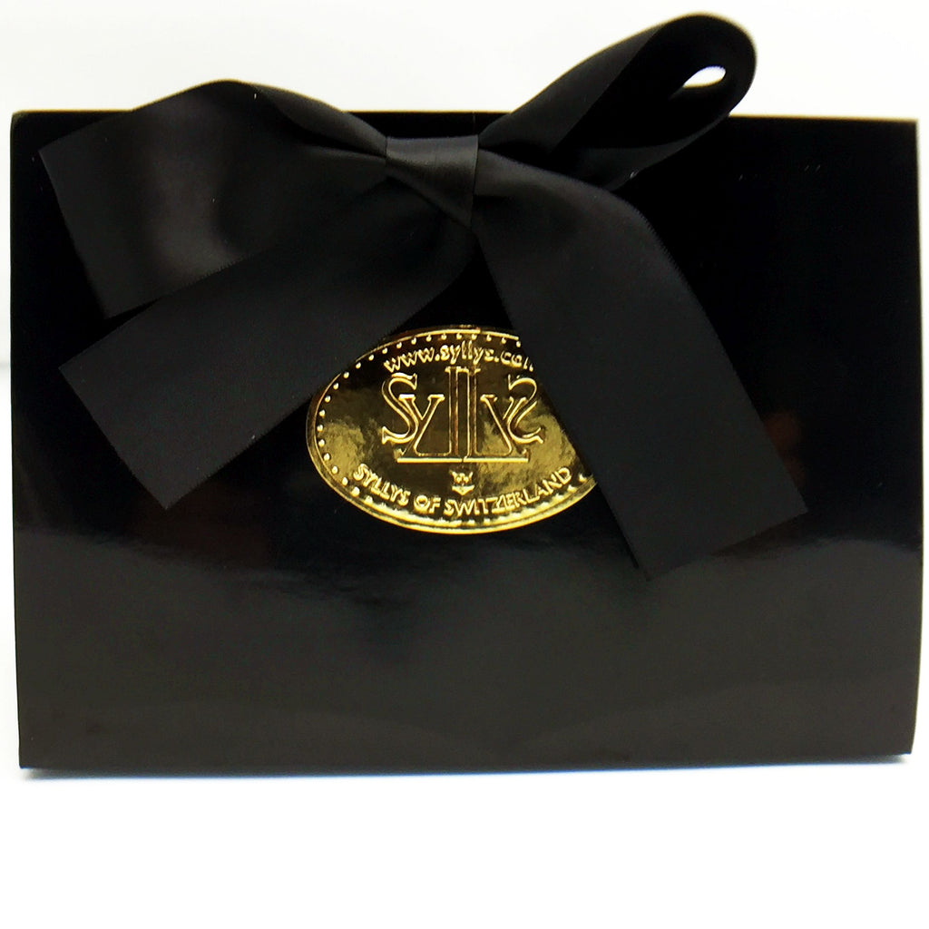 A beautiful black like vinyl gloss gift box tied with a black ribbon with Syllys of Switzerland gold label printed on the front offered as a free gift wrapping.