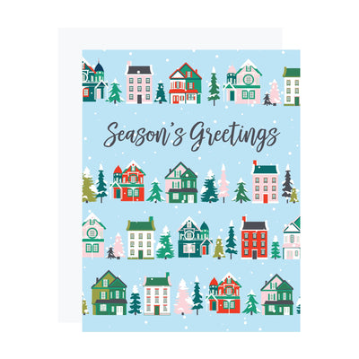 Season's Greetings Christmas card with Victorian houses and evergreen trees. REVEL & Co.