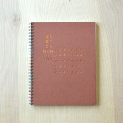 Revel Paper sketchbook with modern copper foil design on terra cotta cover. Revel Paper for the modern desk.