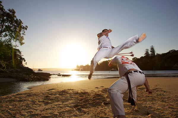 Men practicing Capoeira on the beach at sunset