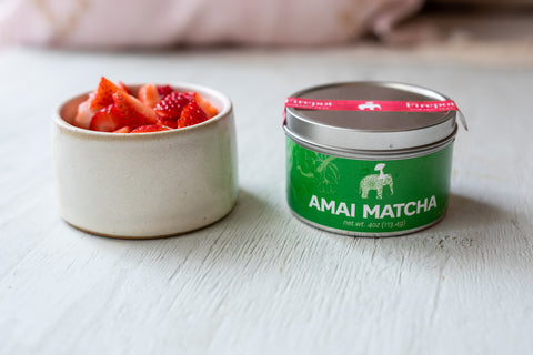 A bowl of sliced strawberries to the left of a tin of Amai matcha