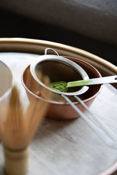 Matcha whisk, cup, and matcha in a sifter