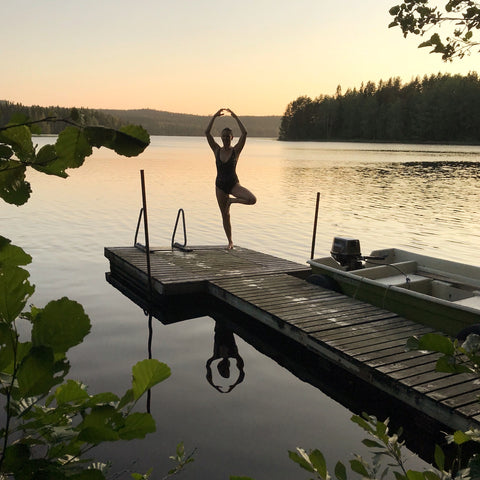 Woman doing yoga on the dock of a lake at sunset