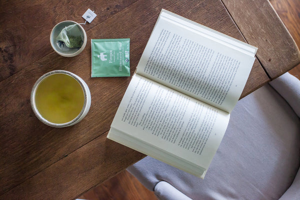 Illuminated Mind matcha green tea on a table with a book