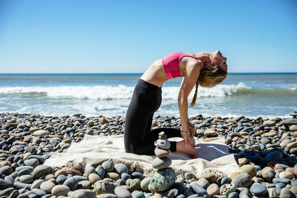 Woman on a rocky beach in the camel yoga pose