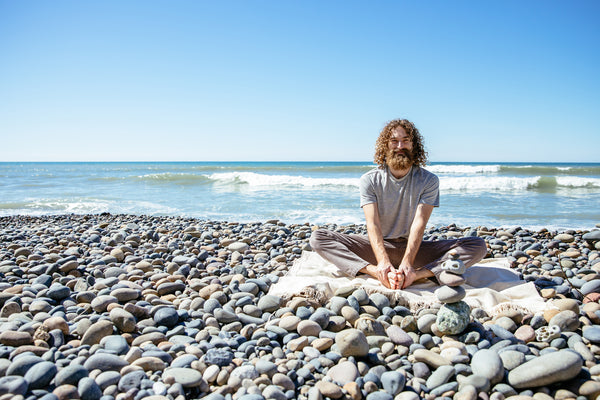 Man sitting on the beach doing the butterfly yoga pose