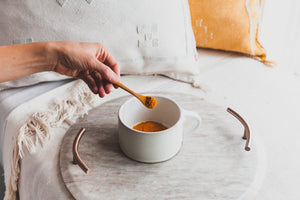 Golden Soul Turmeric Powder in a white mug in a wooden spoon