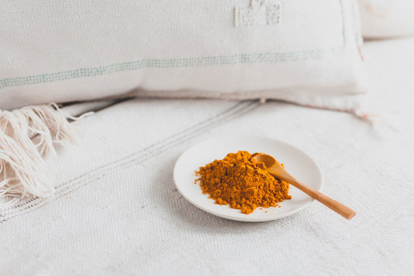Golden Soul Turmeric powder with a wooden spoon on a white plate.