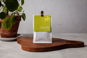 2oz bag of loose leaf yerba mate standing on a wooden board