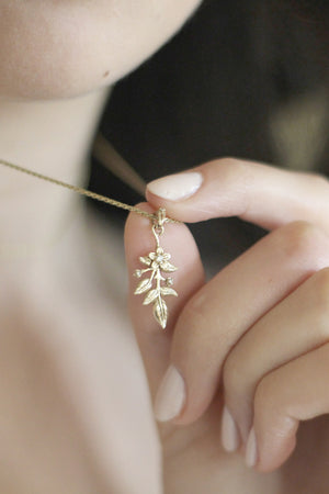 14 karat yellow gold leaf necklace with a flower, leaves, vine, and diamonds