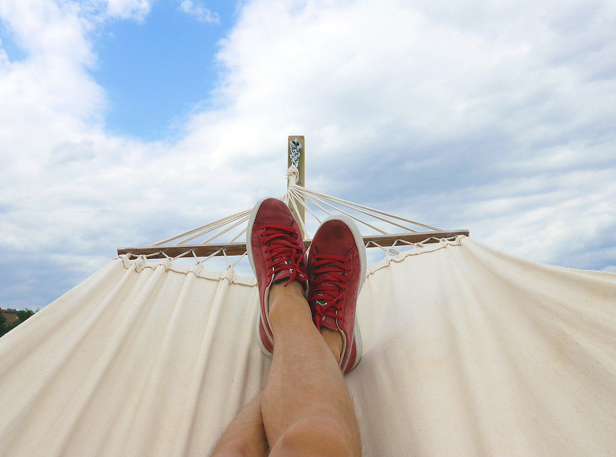 A person's legs on a hammock.