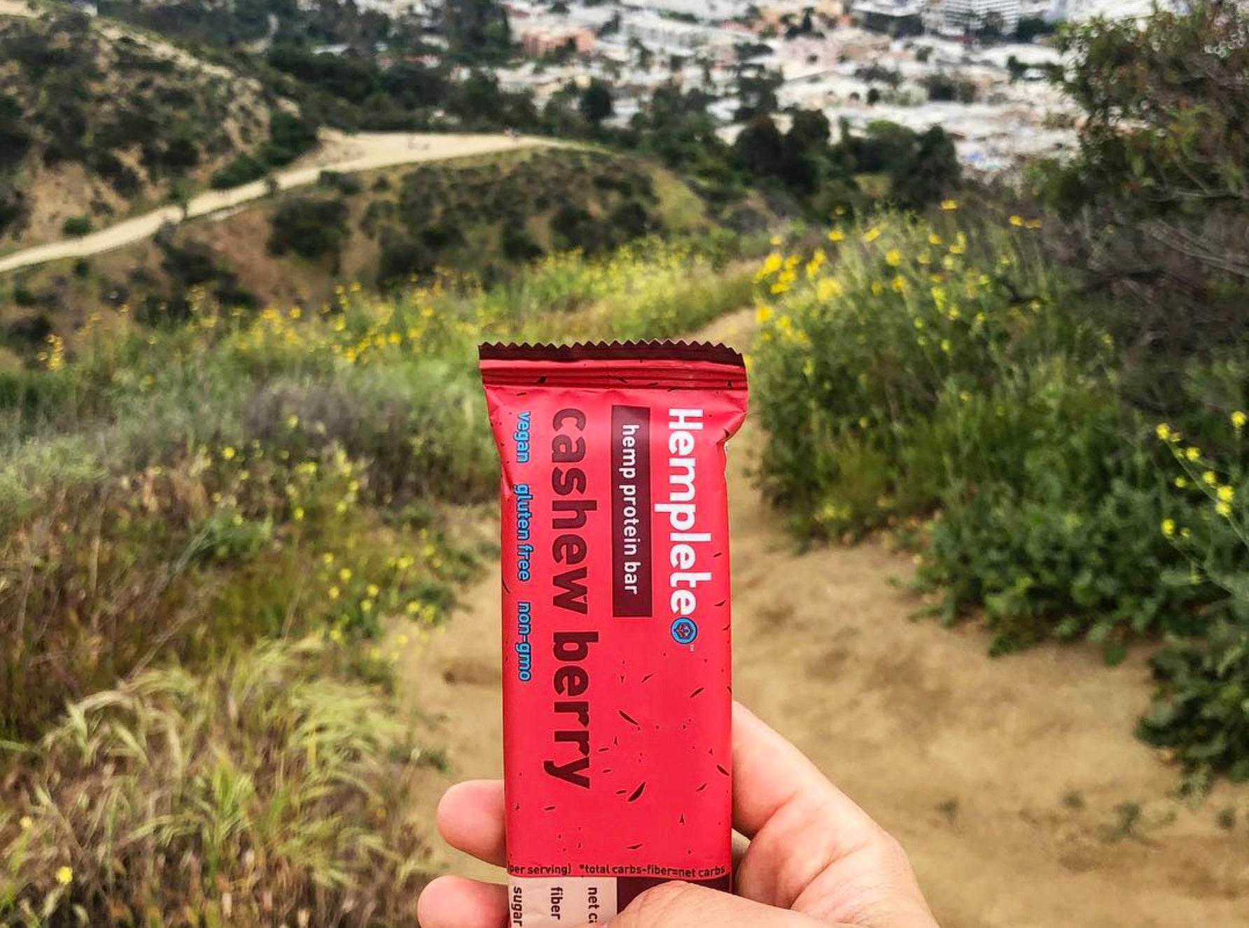 A hemp protein bar held up in front of trails